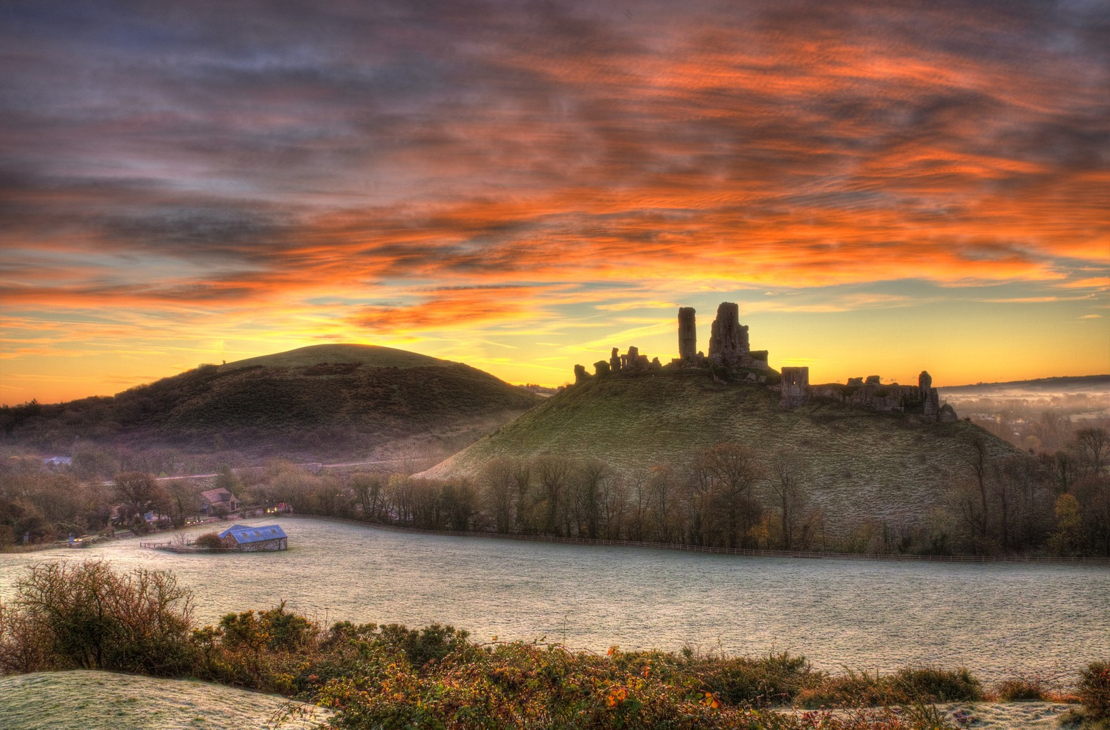 Castles in Dorset - ruins of Corfe Castle againt a sunrise