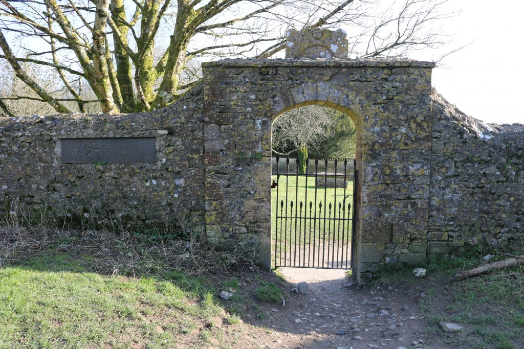 stone archway with iron gate leading to a graveyard