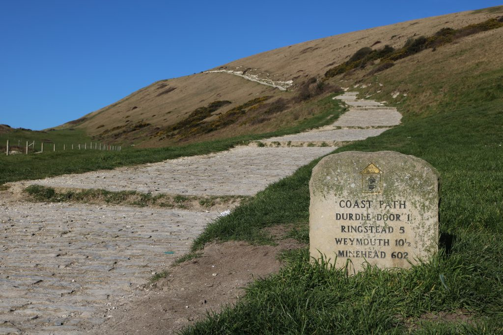 Stone signpost for the South West Coast Path in Dorset